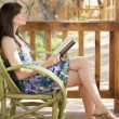 A pretty woman is sitting on a chair and reading book — Stock Photo #22156441
