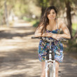 Portrait of pretty young woman with bicycle — Stock Photo