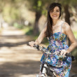 Stock Photo: Portrait of pretty young woman with bicycle