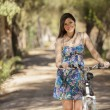 Portrait of pretty young woman with bicycle — Stock Photo #22156491