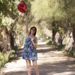 Young woman standing in park with the red heart-shaped balloon  — Stockfoto