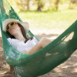 Stock Photo: Young girl sleeping in a hammock