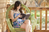 A pretty woman is sitting on a chair and reading book — Stock Photo