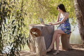 Portrait young charming woman laptop sitting stump — Stock Photo