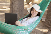 Girl with a laptop in a hammock — Stock Photo