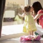 mladá matka vyhlíží z okna s dítětem — Stock fotografie