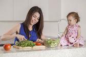 Brunetka matka a dcera připravit salát v kuchyni — Stock fotografie