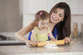 Mother and daughter using a rolling pin together in the kitchen — Stock Photo