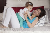 Brunette vrouw spelen met haar baby op een bed in haar appartement — Stockfoto