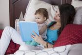 Moeder en dochter in bed lezen van boek — Stockfoto