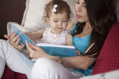 Mother and daughter in bed reading book — Stock Photo