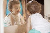 Cute baby looking into mirror — Stock Photo