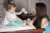 Kärleksfull mor sätta skor på baby på soffan hemma — Stockfoto