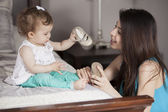 Loving mother putting shoes on baby on sofa at home — Stok fotoğraf