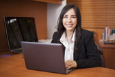 Businesswoman sitting at table in office lobby and using laptop — Stock Photo