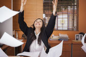 Young woman and flying papers in office — Stock Photo