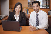 Businessman and businesswoman sitting at desk at work — Stock Photo