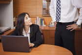 Young attractive woman sitting in office at desk, looking at man, man standing — Stock Photo