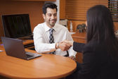 Businessman shaking hands with a Businesswoman in an office — Stock Photo