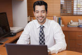 Portrait of a happy successful mature business man working with laptop in a wood paneled office — Stock Photo