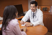 Male Doctor writing something down while patient is talking in a room — Stock Photo