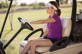 Smiling female golfer driving golf cart — Stock Photo