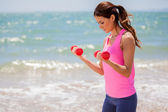 Young girl doing exercises with dumbells — Stock Photo
