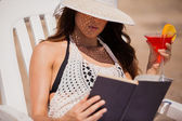 Beautiful woman reading a book on beach — Stock Photo