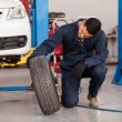 Male mechanic at a car garage fixing a wheel — Stock Photo #26934529