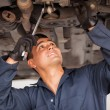 Stock Photo: Car mechanic examining car suspension of lifted automobile at repair service station