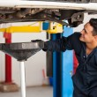 Car mechanic examining car suspension of lifted automobile at repair service station — Stock Photo #26934627