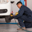 Male mechanic at a car garage fixing a wheel — Stock Photo #26934693