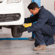 Male mechanic at a car garage fixing a wheel — Stock Photo