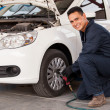 Stock Photo: Male mechanic at a car garage fixing a wheel
