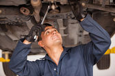Car mechanic examining car suspension of lifted automobile at repair service station — Stok fotoğraf