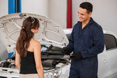 Mechanic standing next to a client in a garage — Stock Photo