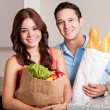 Couple carrying groceries and bread into the kitchen — Stock Photo