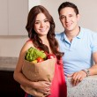Woman and her partner carrying a bag of groceries in the kitchen — Stock Photo