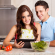 Stock Photo: Couple looking for a dinner recipe in tablet computer