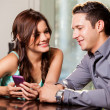 Woman showing something to her boyfriend on her cell phone — Stock Photo