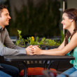 Couple holding hands across a table — Stockfoto
