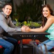 Couple holding hands across a table — ストック写真