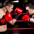 Stock Photo: Two young boxers facing each other in match