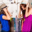 Two women trying on hats — Stockfoto