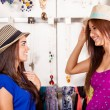 Two women trying on hats — Stock Photo