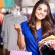 Young woman in a shop buying clothes — Stock Photo #30713209