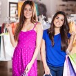 Two happy women shopping in clothes store — ストック写真