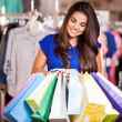 Smiling girl with shopping bags in shop — Stock Photo