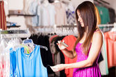 Modern woman shopping holding smartphone — Stock Photo