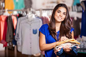 Young woman in a shop buying clothes — Stock Photo